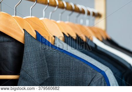 Suits For Men Hanging On The Rack. Mens Suits In Different Colors Hanging On Hanger In A Retail Clot
