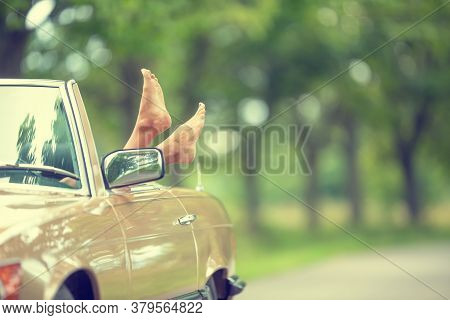 Bare Feet Sticking Out Of A Cabrio Vintage Car Parked In The Nature.