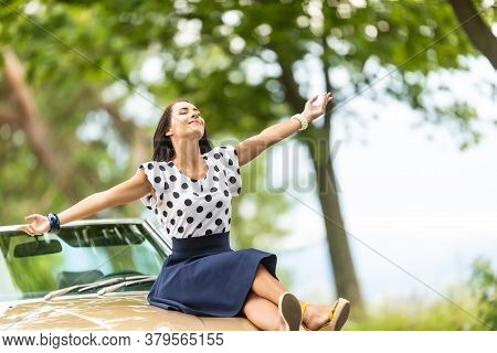 Woman In Polkadot Blouse And Skirt Sits On A Bonnet Of A Cabrio Car, Arms Open, Enjoying Summer.
