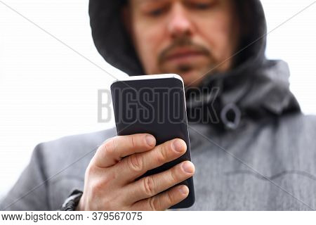 Married Man In Hood Holds And Looks At Smartphone. Reading News On Phone. Communication Through Inst