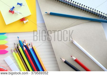 Top View Of Colourful Set Of Pencils For Drawing. Empty Sheet On Table. Pins With Bright Covers And