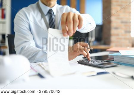 Close-up Of Accountant Specialist Sitting In Office With Calculator And Paper Checks. Man In Present
