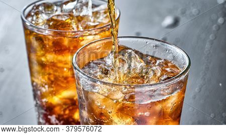 two cups of cola soft drink being poured into glass
