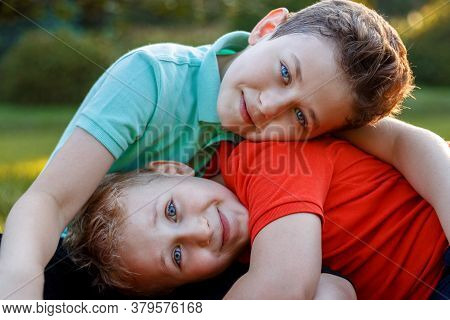 Frontal Portrait Of A Cheerful Two Brothers Stand Together In A Hug At The Park.