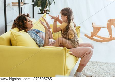 Babysitter And Child Playing Pat-a-cake Game While Having Fun On Sofa