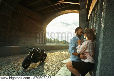 Love And Romantic Concept. Couple In Love With Sunset Stand By The Wall Kiss And Hug Under The Bridg