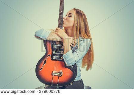 Young Devoted Woman Sitting On Gray Background And Kissing Electric Guitar
