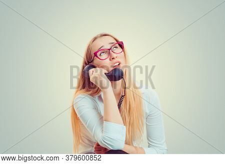 Young Blond Woman In Eyeglasses Looking Up In Boredom And Irritation While Speaking On Telephone