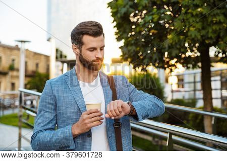 Image of young handsome businessman holding coffee cup and looking at his wristwatch outdoors