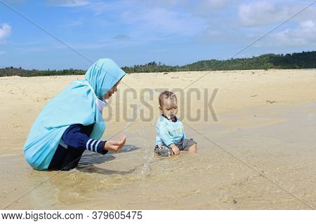 A Beautiful Cute Indonesian Baby Play With Her Mom On The Beach