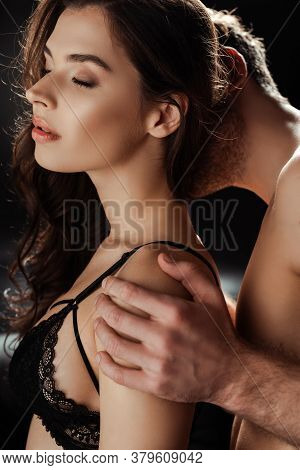 Shirtless Man Kissing Neck And Hugging Beautiful Woman In Bra On Black