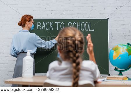 Back View Of Schoolgirl With Raised Hand, And Teacher In Medical Mask Writing On Chalkboard With Bac