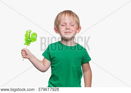 Child Boy 4 Years Old In A Green T-shirt Holds Lollipop Cock On Stick. The Kid Closed His Eyes Happi