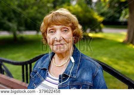 Portrait Of An Elderly Woman With Headphones Looking At Camera Against Green Grass And Smiling.