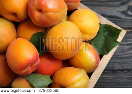 Many Fresh Ripe Apricots In Wooden Crate On Table, Closeup