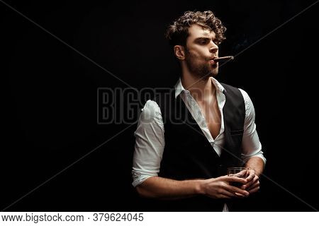 Handsome Man In Shirt And Waistcoat Holding Glass Of Whiskey And Smoking Cigar Isolated On Black Bac