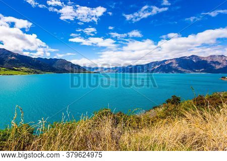 Fabulous country of New Zealand. Mountains surround a magical lake Hawea. Turquoise smooth water of the lake decorate the South Island. The concept of ecological, phototourism and active tourism