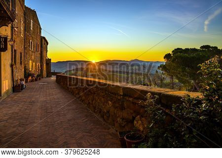 The early dawn. The stunning landscape of the valley is photographed from a protective wall around the city. Tuscany. The concept of active, architectural and photo tourism