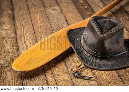 blade of wooden canoe paddle (beaver tail) and outback oilskin hat against weathered wood background