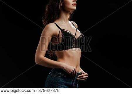 Cropped View Of Woman In Lace Bra Touching Jeans Isolated On Black Background