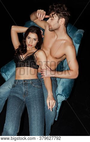 High Angle View Of Woman In Bra And Jeans Looking At Camera Near Boyfriend On Armchair Isolated On B