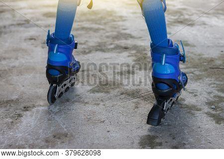 Little Boy Learning Roller Skate By Wearing Blue Roller Skate Shoes On Cement Floor