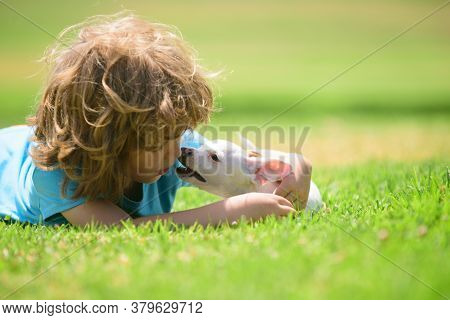 Cute Boy Child With Her Doggy Lying On Lawn. Kid With Pet Puppy Dog. Emotions Of People