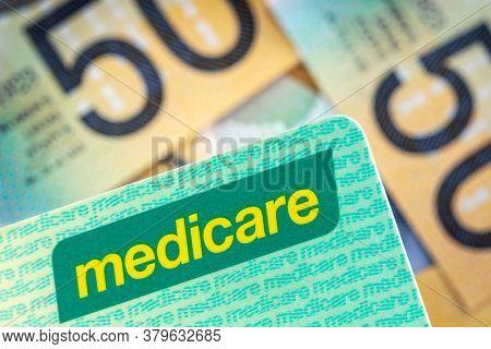 Australian Medicare card over blurred money background.