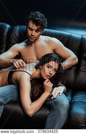 Handsome Man Touching Back Of Beautiful Woman In Bra On Couch On Black