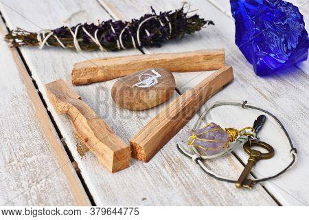 A Close Up Image Of Three Palo Santo Smudge Sticks With A Home Made Pendulum.