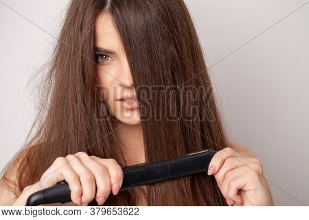 Woman With Beautiful Long Straight Hair Using A Hair Straightener