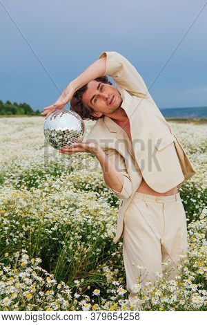Tall Handsome Man Standing In Camomile Flowers Field Holding Mirror Disco Ball.