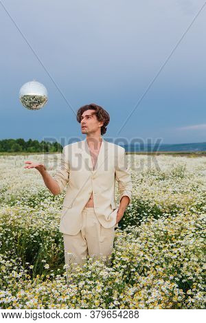 Tall Handsome Man Standing In Camomile Flowers Field Throwing Up Mirror Disco Ball.