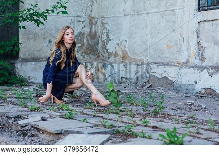 Young Woman Sitting Next To An Old Building With Grey Walls