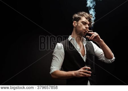 Man In Shirt And Waistcoat Smoking Cigar And Holding Glass Of Whiskey Isolated On Black Background