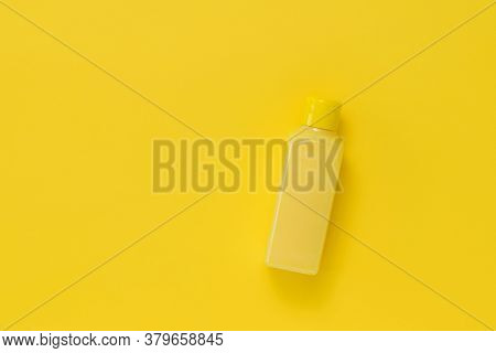 A Yellow Plastic Bottle With A Yellow Liquid On A Yellow Background. Plastic Utensils For The Storag