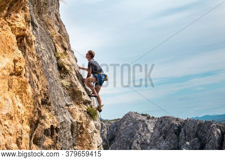 Rock Climber On The Background Of Mountains And Sea. A Man Climbs On A Rock. Training In Nature. Act