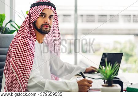 Handsome Confident Arab Businessman Working And Looking At Technology Of Laptop Computer Monitor.cre