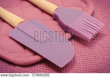 Closeup Of Silicone Kitchen Accessories, Spatula And Brush Lying On Purple Cloth