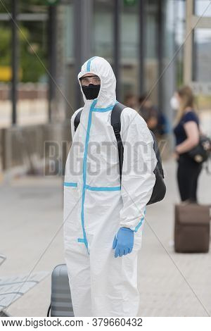 Man Wearing A Full Protective Suit, Glasses And Face Mask Waiting At A Train Station While Keeping A