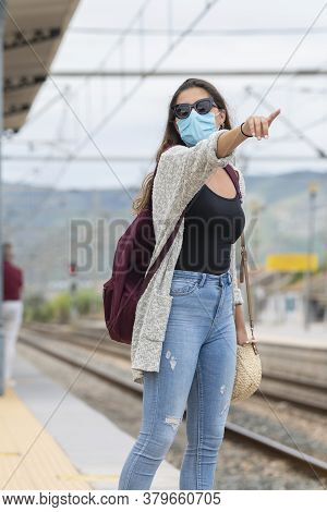 Young Woman Using Glasses And Surgical Mask Pointing Somewhere While Waiting At A Train Station
