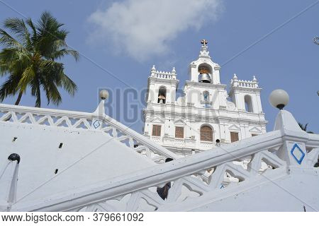 Church Of Our Lady Of Immaculate Conception In Goa With Blue Cloud Background And Green Tree