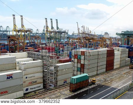 Singapore, March 8, 2016: Transport Truck Moves Two Containers In The Storage Area. Dozens Of Stacke
