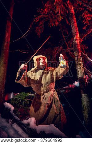 Medieval Monk In Canvas Sackcloth Robe With Sword And Lattern In Dark Forest And Red Light Of Moon O