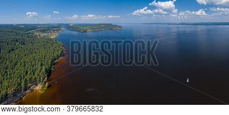 Aerial panorama of the calm river of Kama, Russia with catamaran sailing on it during summer day