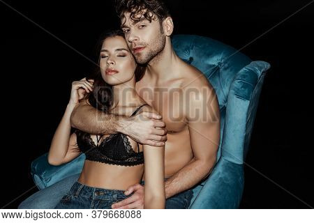 Handsome Shirtless Man Embracing Woman In Bra On Armchair Isolated On Black Background