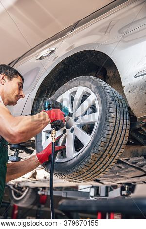 Car Mechanic Remove Or Install Wheel Nut In His Garage