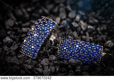 Close Up Of Silver Jewelry Earrings With Small Blue Stones On Coal Background