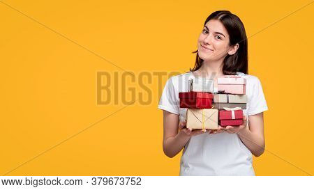 Holiday Sale. Special Offer. Cheerful Woman In White T-shirt Holding Gift Boxes Pile Isolated On Ora