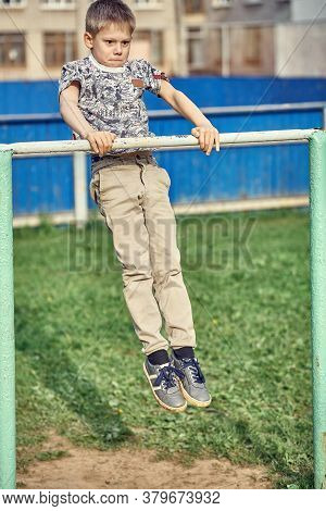 Strong Kid Doing Muscle Up On Sports Ground